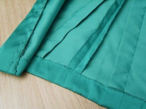 Hemline and front-facing hand-secured on inner tafeta layer.