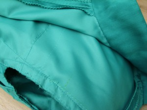 Collar and rear-fold secured on tafeta, layers locked together in arm-hole.