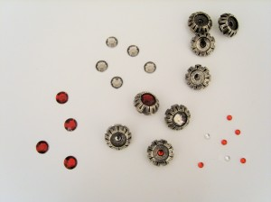 Cathedral Cape decorative buttons with four different sorts of rhinestone layed out to embed.