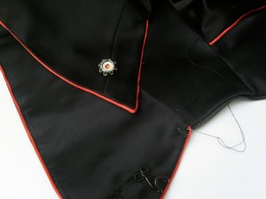 Satin rat-tail trim-cords, one embedded within the neckline, the other worked into the mid-collar seam.