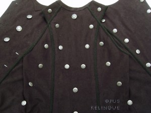 Gothic vest-coat, rhythmically decorated with ornate buttons.
