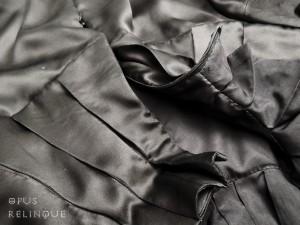 Hidden zipper within a pleated collar.